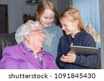 Small photo of A 95-year-old woman laughs at her 7-year-old and 9-year-old great-granddaughter. She is sitting on a chair in her living room. The two girls are standing. The younger girl is holding a tablet