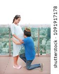Small photo of Asian man wearing crown and kneel with kissing tummy of pregnant woman on the roof of building.