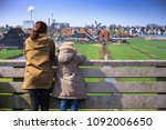 the sisters look at wind mills... | Shutterstock . vector #1092006650