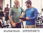 personal trainer giving advice... | Shutterstock . vector #1092053873