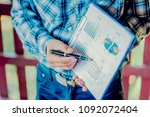 Small photo of Business meeting, man's hands pointing on charts. Reflection light and flare. Concept image of data gathering and statistical working.