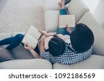 Small photo of Top view portrait of well-read lettered couple enjoying reading novel poem, poetry fans, lying on sofa having books in hands. Hobby free time self-development education concept