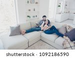Small photo of Portrait of stylish attractive couple enjoying reading novel, poem, poetry, lying on sofa having books in hands, woman telling showing comic plot from her detective story