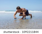 Small photo of Muscular Caucasian man doing bear crawl workout on sandy beach on sunny day at lowtide