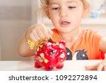 girl putting coins her piggy... | Shutterstock . vector #1092272894