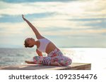 younger woman playing yoga pose ... | Shutterstock . vector #1092354476