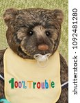 Small photo of A brown teddy bear with pacifier in mouth and wearing a yellow bib. Knitted green background.