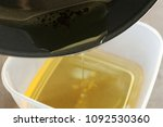 pouring used cooking oil from... | Shutterstock . vector #1092530360