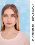 Small photo of Confident glance. Portrait of young good looking light haired girl having calm facial expression while standing against sky blue background flowery design