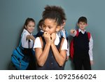 Small photo of Children bullying African-American girl on color background