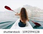 woman paddling a canoe through...   Shutterstock . vector #1092594128
