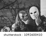Small photo of Girl and man hide face with masque. Woman with long blond hair and bearded hipster in mask at window. Carnival, masquerade, holiday celebration. Decoration, amusement, disguise, pretense concept.