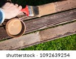 Small photo of Close up of hand staining wooden furniture with brush and brown protective wood stain, repainting old terrace furniture in spring. Refreshing, giving new look concept.