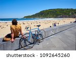 Small photo of San Sebastian, Spain - May 11, 2018. A young men with their bike parked in front of Zurriola beach and Monte Ulia in background at sunny day. San Sebastian, Guipuzcoa. Spain.