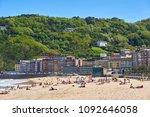 Small photo of San Sebastian, Spain - May 11, 2018. People enjoying a sunbathing in Zurriola beach with Monte Ulia in background. San Sebastian. Basque Country, Guipuzcoa. Spain.