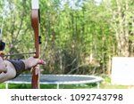 Small photo of A man shoot away an arrow with a bow. Concept for sunny summer day, games, puncture, dot sure, hit the right spot etc.