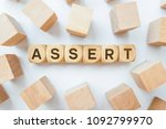 Small photo of Assert word on wooden cubes
