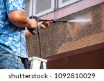 Man using High Power Pressure Water for Smash Cleaning Dirty Wall outdoor. - stock photo