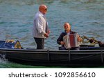 Small photo of Venice, Italy - September 23, 2017: Man serenades gondola riders to an accompaniement of an accordeon