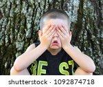 little boy sitting outdoors...   Shutterstock . vector #1092874718