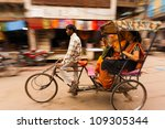 Small photo of Mathura, India - November 13, 2009: Blurred panning shot of two Indian women laughing while riding a cycle rickshaw, a popular form of taxi, through a busy bazaar