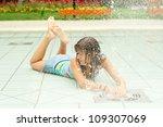 Teenage girl having fun in the water fountain on hot summer day.