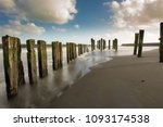 Small photo of Patea's posts in the sand
