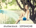 Teen girl near lake in the park. - stock photo
