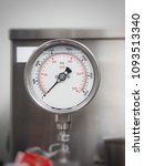 Small photo of A industrial pressure gauge use for measuring a force by a fluid on a surface. A pressure gauge reading in metric unit, bar, is shown in red while pounds per square inch, psi, is shown in black.
