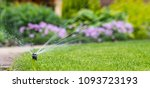 automatic sprinkler system watering the lawn on a background of green grass - stock photo