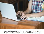 using the notebook on a wooden... | Shutterstock . vector #1093822190