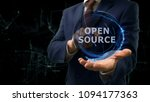 Stock photo businessman shows concept hologram open source on his hand man in business suit with future 1094177363