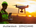 Drone inspection. Operator inspecting construction building site flying with drone. sunset - stock photo
