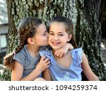 two sisters sit outside besides ... | Shutterstock . vector #1094259374