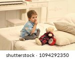 Small photo of Kids playing with toys. Child in bedroom with silence gesture. Kid put plush bear near pillows and alarm clock, luxury interior background. Time to sleep concept. Boy with calm face puts favourite toy
