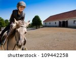 Stock photo horseback riding lovely equestrian little girl is riding a horse 109442258