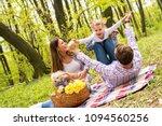 happy parents enjoying picnic... | Shutterstock . vector #1094560256