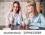 two smiling girlfriends drinks... | Shutterstock . vector #1094613089