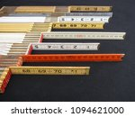 Small photo of Metric and inch folding rulers arranged with copy space illustrate accuracy, precision and measurement.