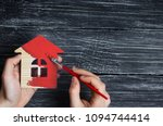 hand paints a house in to red... | Shutterstock . vector #1094744414