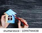 hand paints a house in to blue... | Shutterstock . vector #1094744438