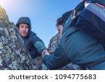 a man helps his friend to climb ... | Shutterstock . vector #1094775683