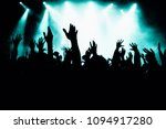 silhouette of raised hands in...