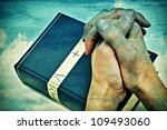 Small photo of someone with hands clapsed praying on a bible
