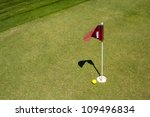 Red flag marks the golf hole on putting range - stock photo