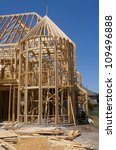 Framed residential construction with unidentifiable worker present - stock photo