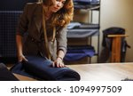 female tailor examines a roll... | Shutterstock . vector #1094997509