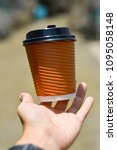 Small photo of Brown hot paper cup of coffee floating from blurry hand in blurry background. In concept an accident can happen at any time, anywhere.