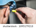 Small photo of Ear Plugs Hearing Protection Simple Solutions. Factory Worker in Blue Hard Hat Preparing To Use Foamy Plug.