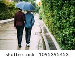 gay couple holding umbrella and ... | Shutterstock . vector #1095395453